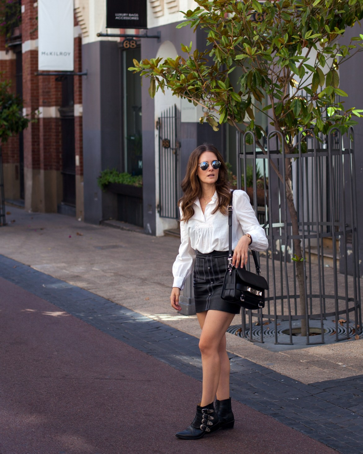 Bohemian Traders blouse, Aje leather mini skirt, Toga Pulla boots, Proenza Schouler Bag and round glasses, street style