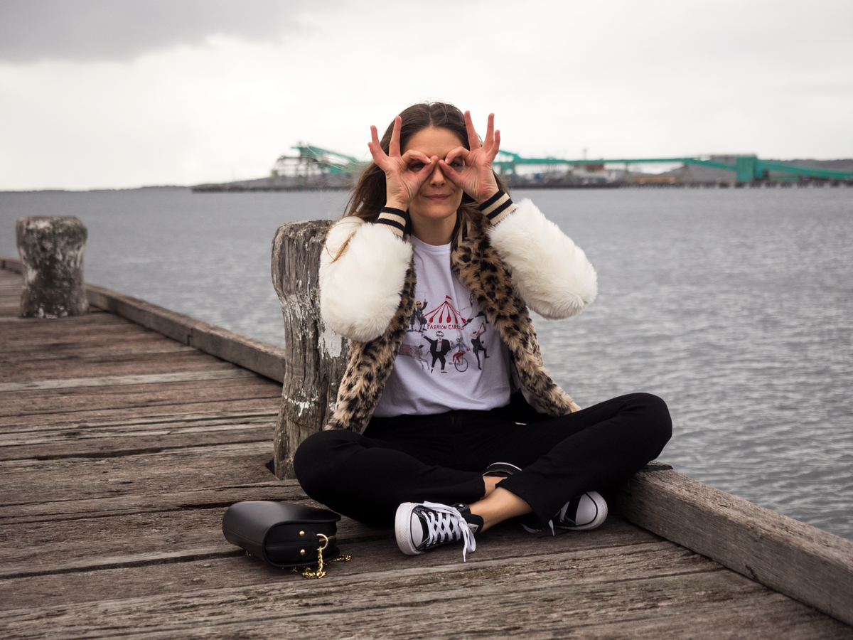 Mother denim leopard faux fur bomber jacket, Unfortunate Portrait Fashion Circus t-shirt, Mavi black jeans, Black Converse sneakers, APC luna half moon bag winter outfit in Port Lincoln. Worn by Jenelle Witty fashion and travel blogger from Inspiring Wit