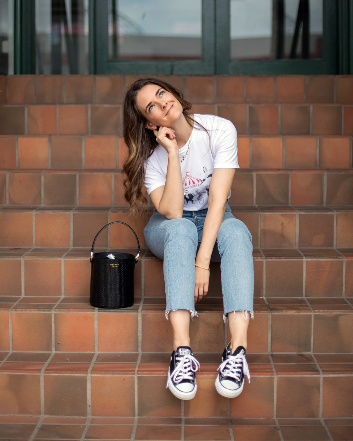 bucket bag outfit ideas featuring Meli Melo Santina bucket bag in black worn by fashion blogger Jenelle Witty from Inspiring Wit. With Unfortunate Portrait graphic tee, Levi's Wedgie jeans and Converse sneakers from Shopbop and Astley Clarke gold Mille Bangle