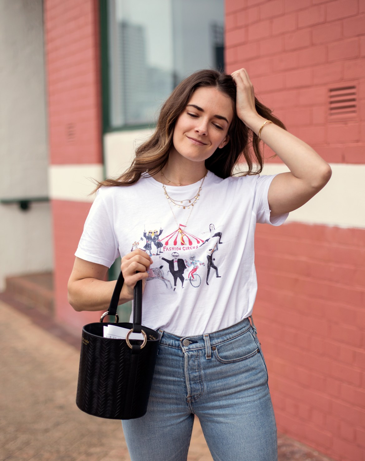 Meli Melo Santina bucket bag in black worn by fashion blogger Jenelle Witty from Inspiring Wit. With Unfortunate Portrait graphic tee, Levi's Wedgie jeans from Shopbop and Astley Clarke gold Mille Bangle