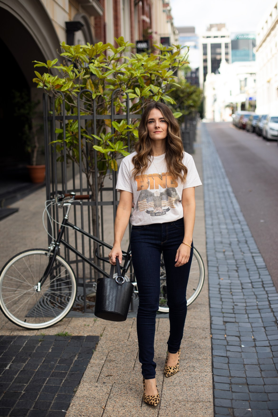 Anine Bing vintage tee outfit with Reiko skinny jeans and leopard print heels worn by fashion blogger Jenelle Witty from Inspiring Wit from a blog post about big little goals to achieve in 2019