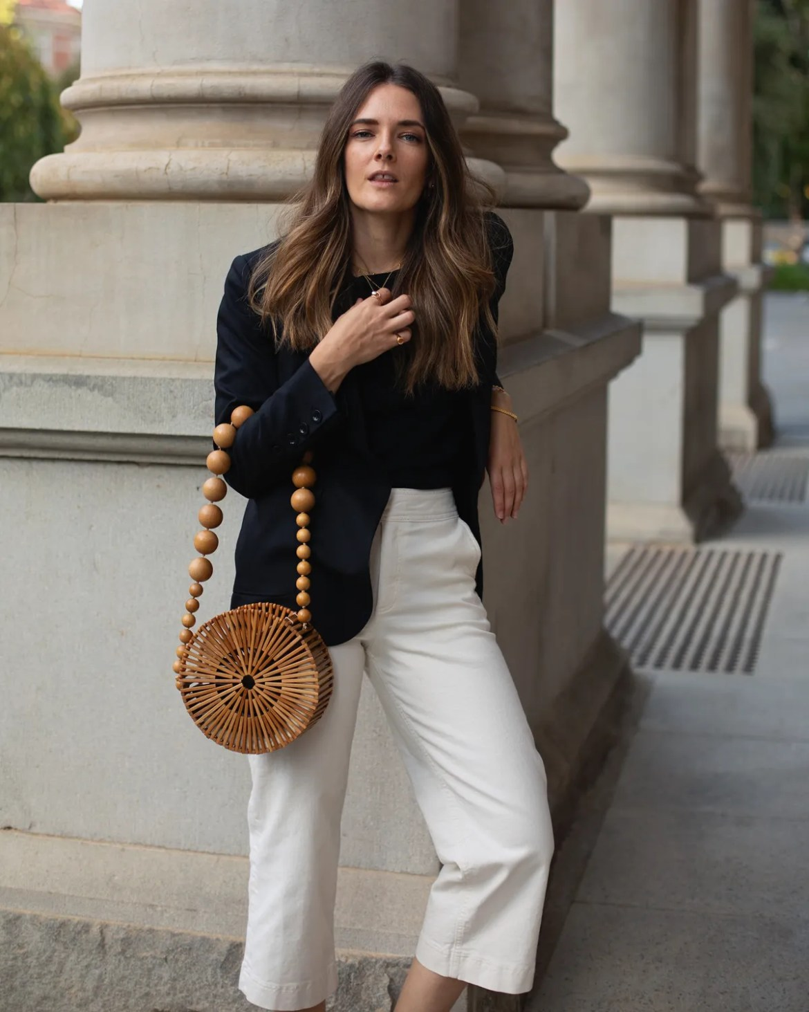 Black blazer, cream pants outfit with bamboo bag