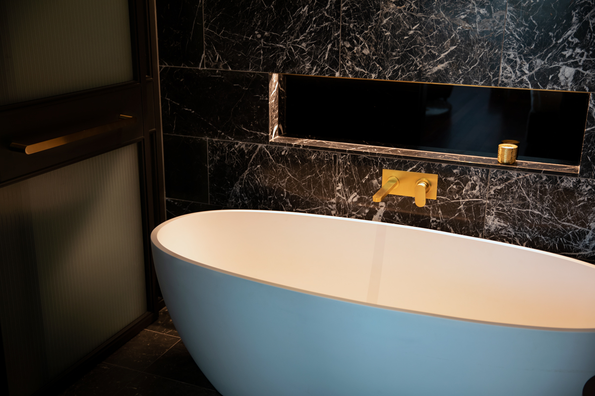 Bathtub in black marble bathroom design