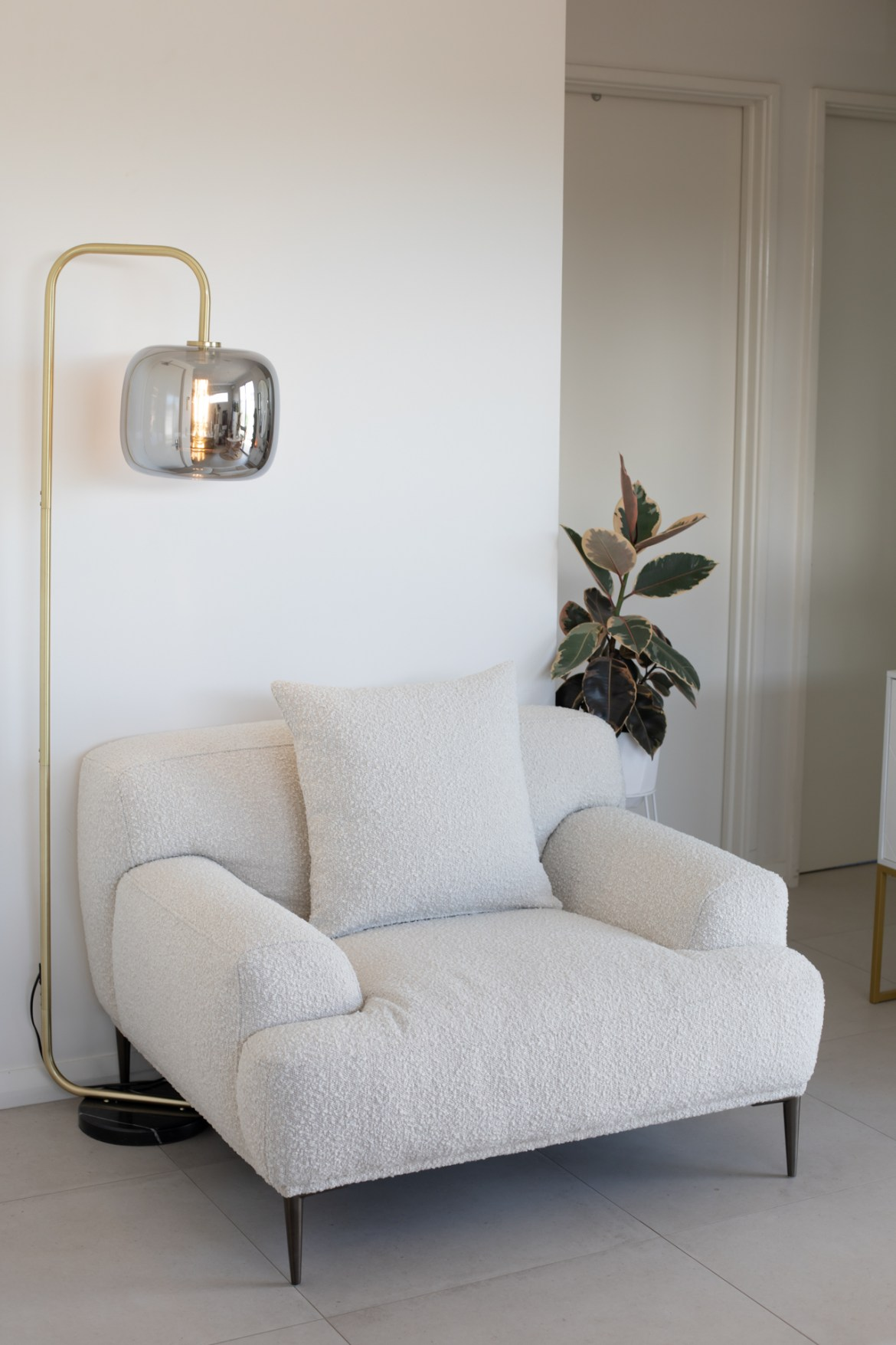 Boucle Seta armchair by Brosa styled at home with brass floor lamp