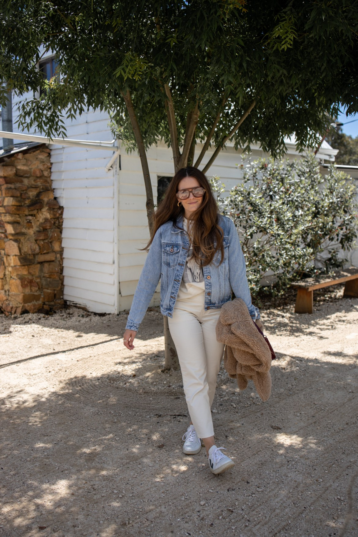 layering outfit with denim jacket and sweater over jeans