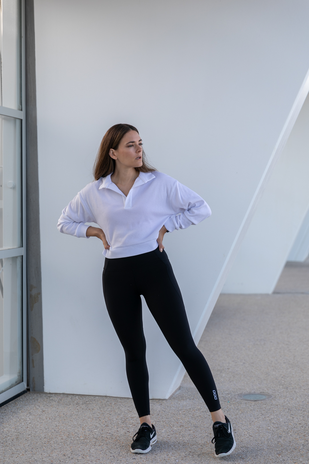 minimal activewear outfit with black leggings and polo top