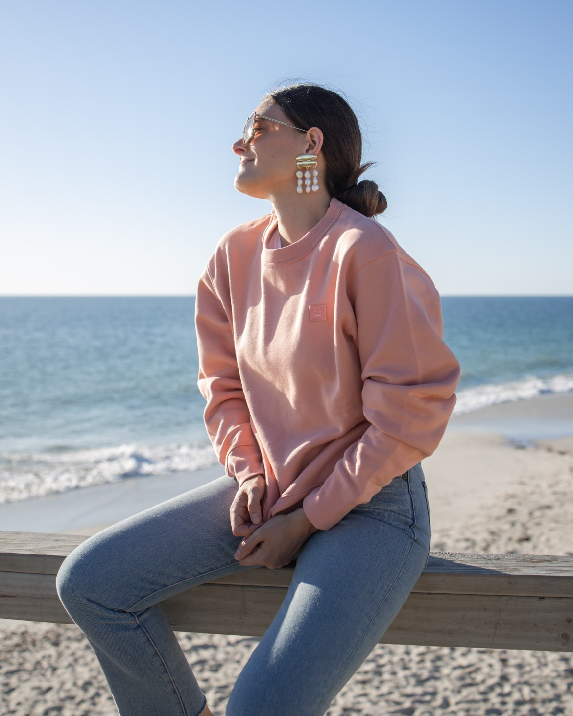 pink Acne Studios sweater at the beach