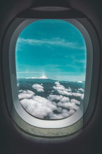 janela de avião com vista para céu azul e nuvens brancas