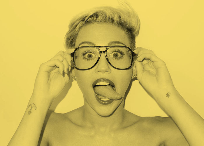 Pop singer Miley Cyrus sticks out her tongue in her signature pose