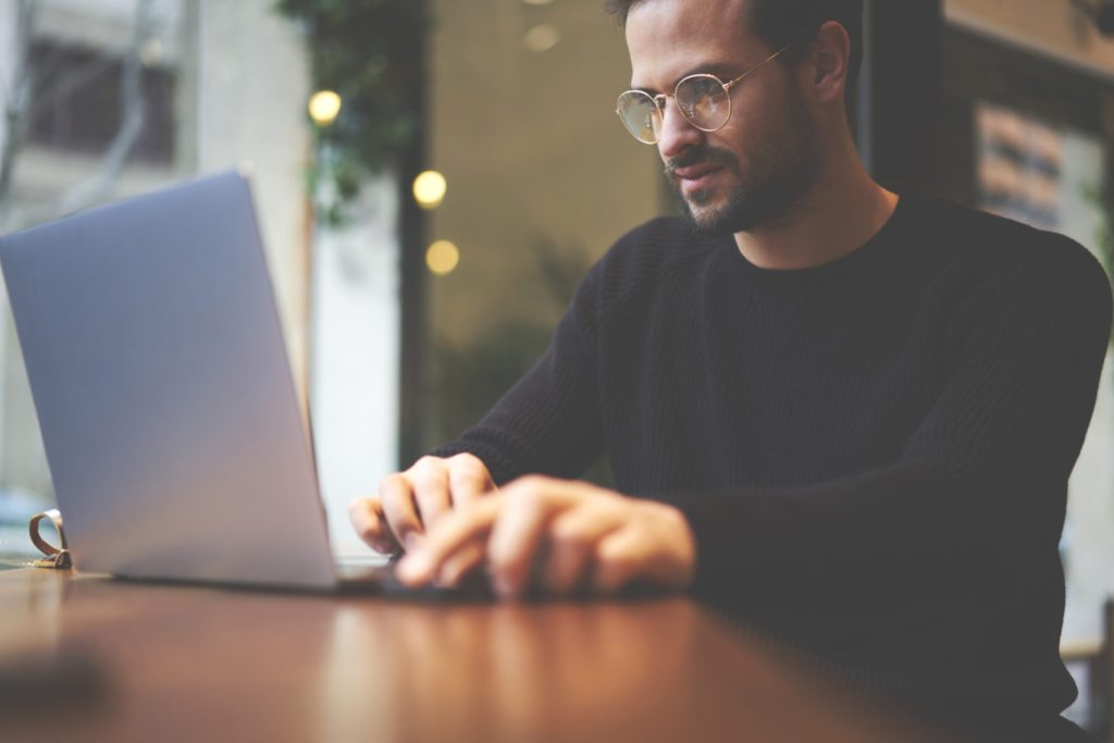 The hybrid cloud, Small business guy with glasses at laptop photo