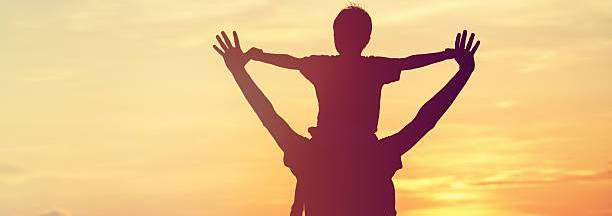 Father holding son with sunset