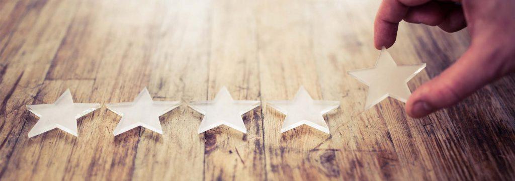 Mano colocando 5 estrellas sobre mesa