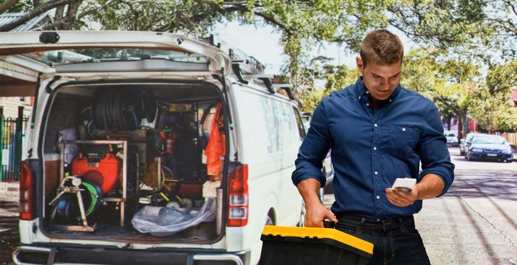 Trabajador saliendo de furgoneta con móvil en la mano