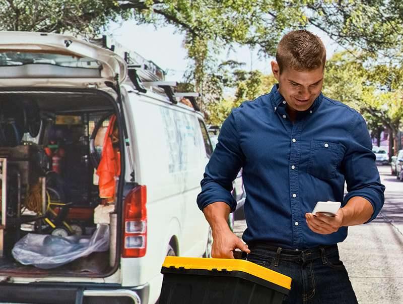 operario consultado su móvil delante de furgoneta