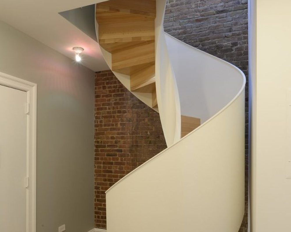 scala elicoidale in legno per casa privata. Struttura bianca con legno laccato e naturale