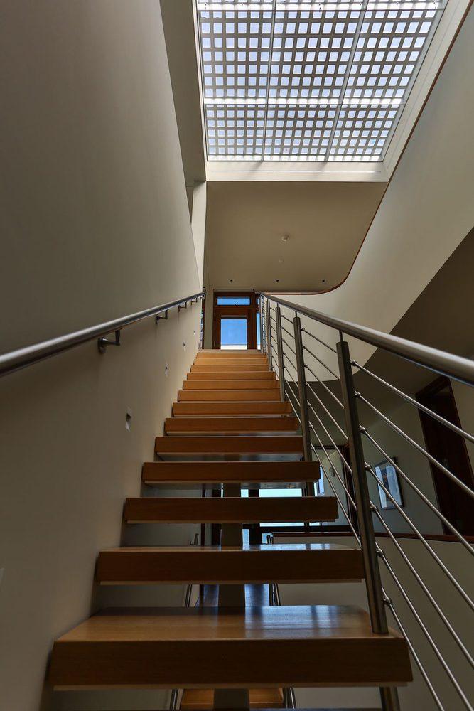 Scala a a giorno in legno e metallo per residenza privata con ringhiera in metallo e corrimano in metallo