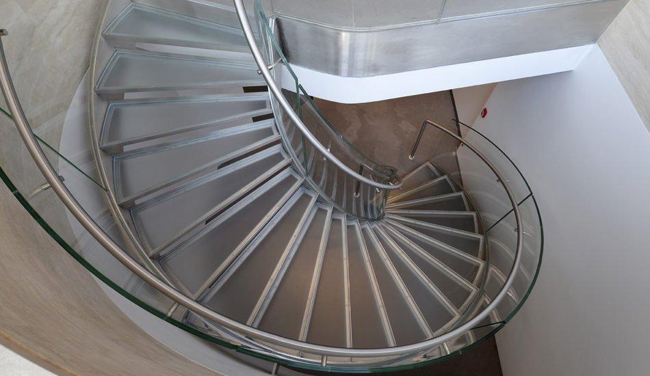 Scala elicoidale ingegnerizzata con doppi fascioni laterali in acciaio inox calandrato, paralleli fra loro. Gradini in vetro triplo strato. Ringhiera in vetro
