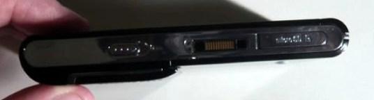 lateral: conector proprietário, slot para microSD, trava para a tela