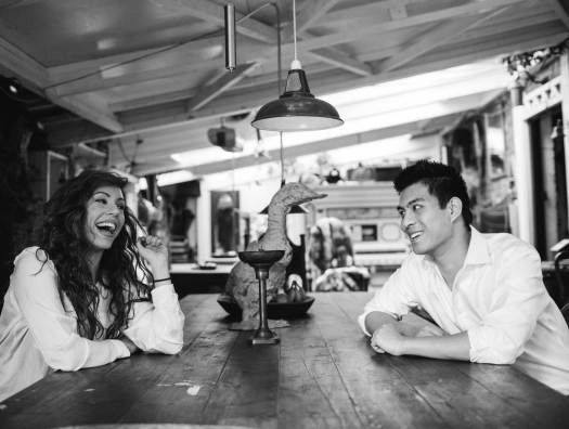 A candid black and white shot of Capioca co-founders, Rebecca Findley and Byron Wong, sitting at a large wooden coffee table and laughing together