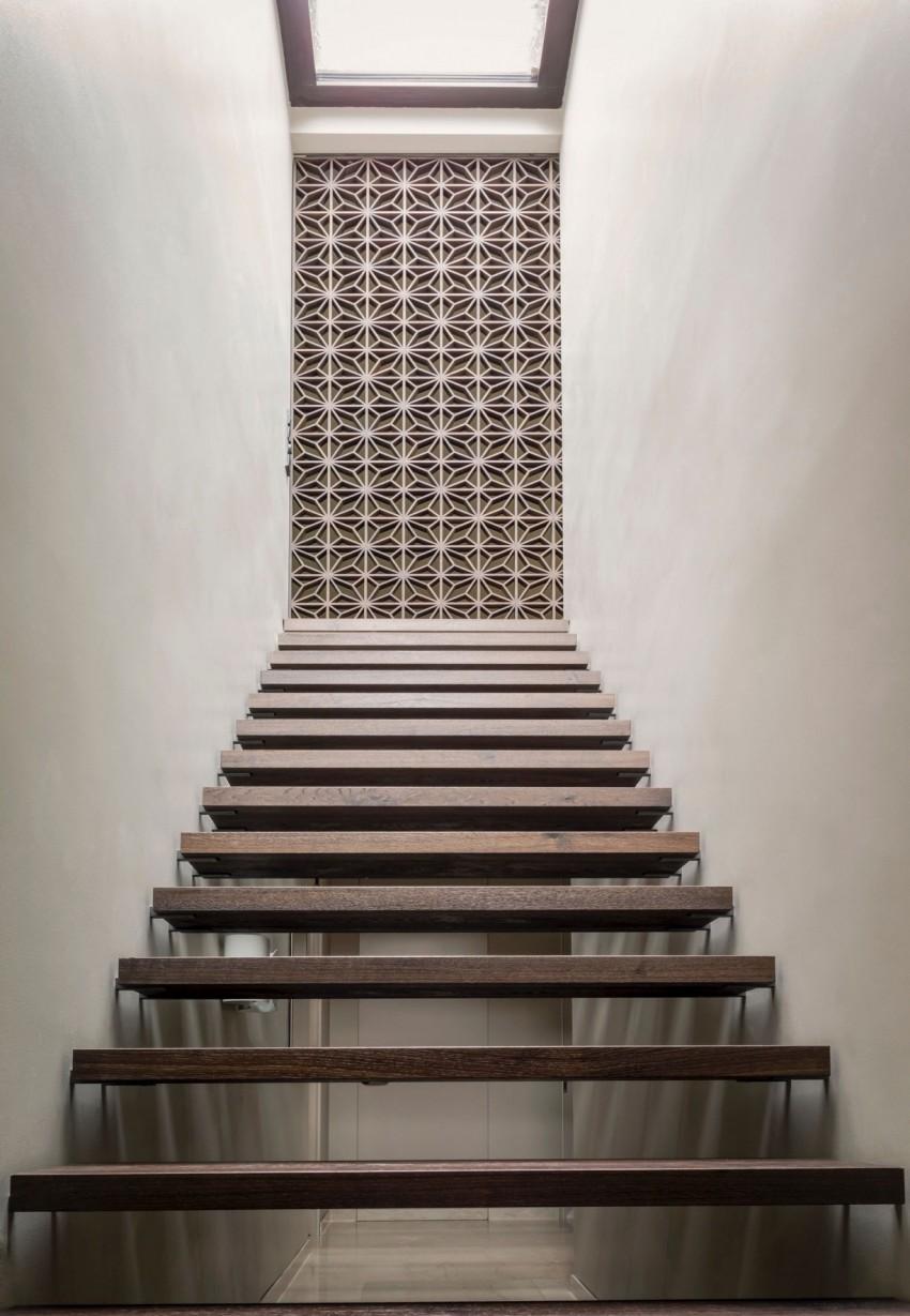 Zwevende houten trap tussen twee dikke muren  Interieur