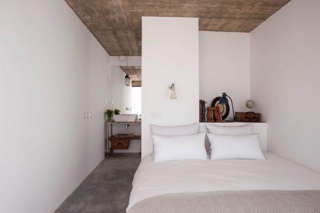 Slaapkamers met strakke witte wanden en betonvloer
