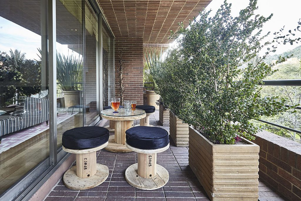Los muebles de la terraza son fabricados a partir del reciclaje de carretes de madera para cables eléctricos, propuesta de Felipe Castellanos. Fotografía: Gabriel Lugo.