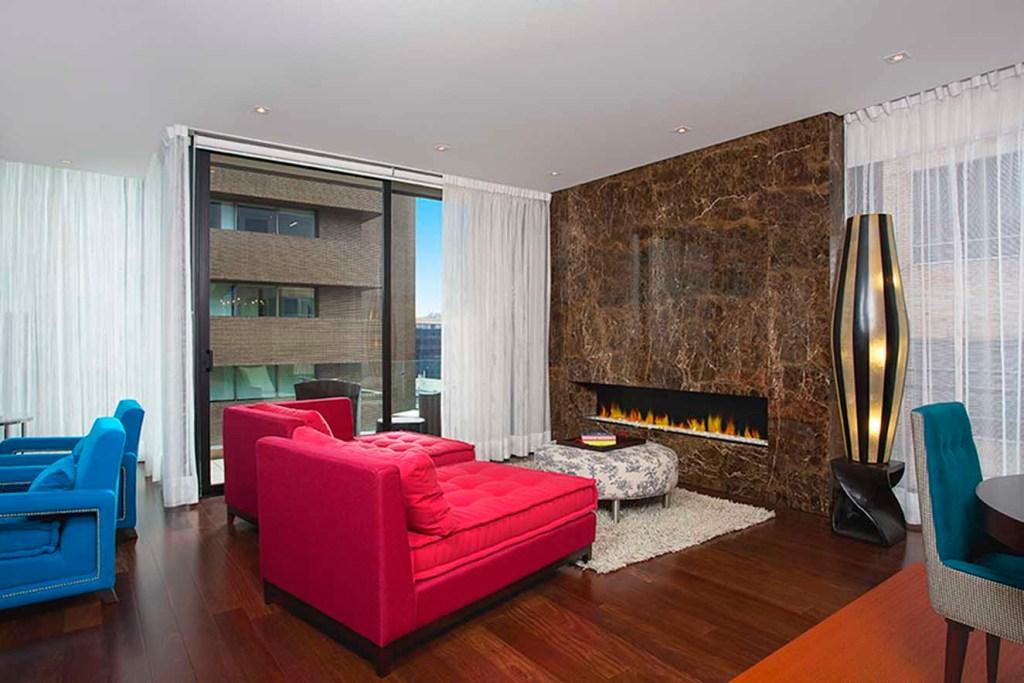 Un llamativo elemento de diseño es la pared recubierta con mármol que alberga la chimenea de gas. El tapete de fieltro es de Mesas&Sillas. Los velos de las cortinas son de malla de Maritel del Nogal. Fotografía: Luis Fernando Ramos.