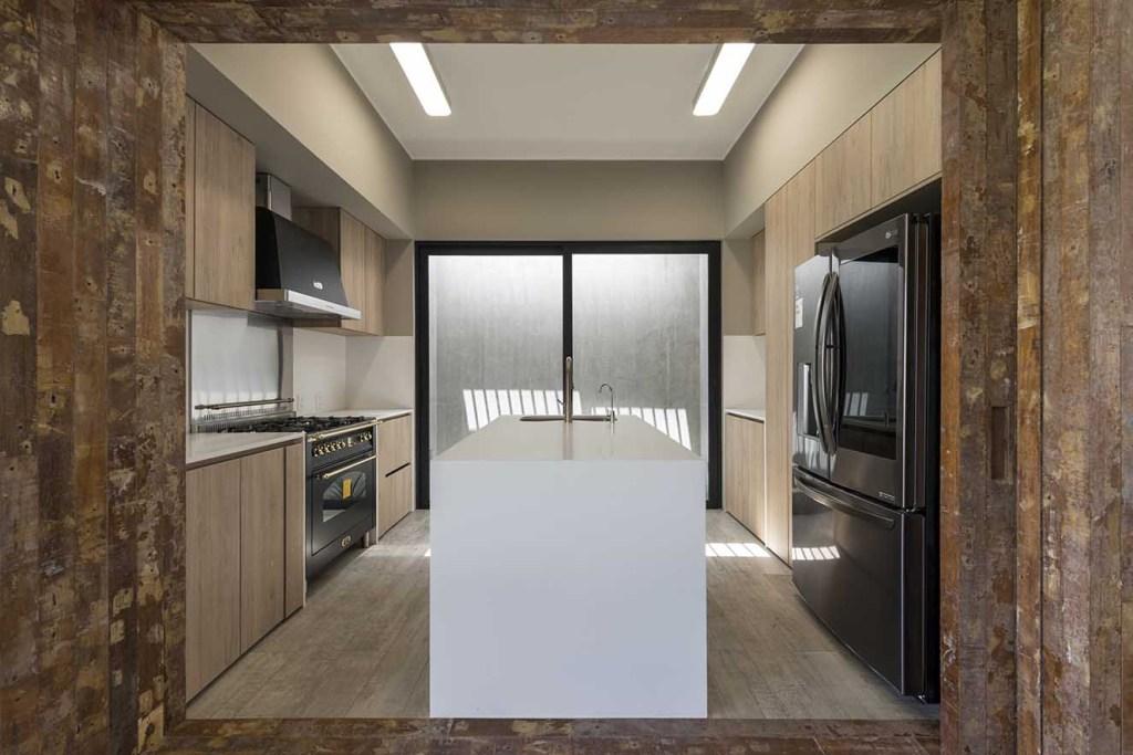 Puertas corredizas de madera rústica permiten abrir la cocina al a´rea social. Se destaca el diseño con isla para mayor funcionalidad y aprovechamiento del espacio. Fotografía: Renzo Rebagliati.