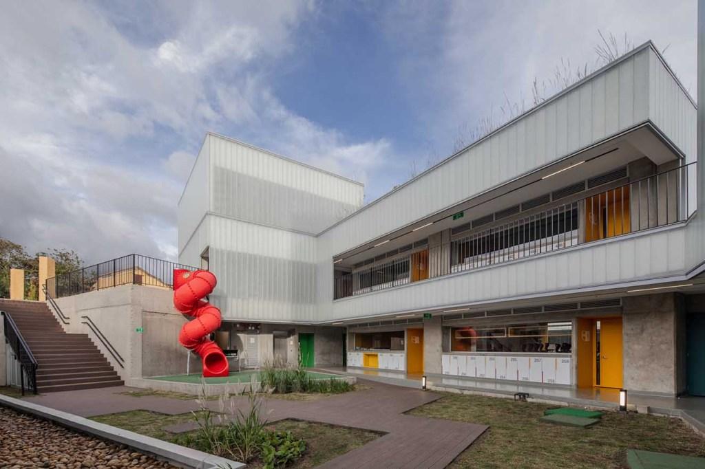 Colegio Helvetia. Vista del nivel inferior. Un rodadero rojo es uno de los elementos lúdicos  del proyecto.