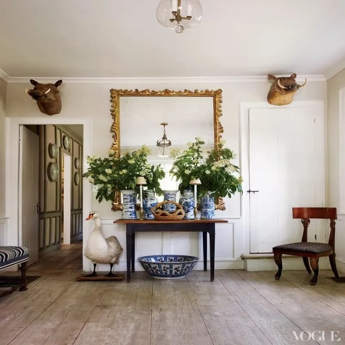 white-interior-hallway-in-minimalist-colonial-style-design-with-stuffed-animals-goose-and-boar-heads-decorations-classic-style-golden-shade-frame-wall-mirror-and-vintage-china-decorative-fl