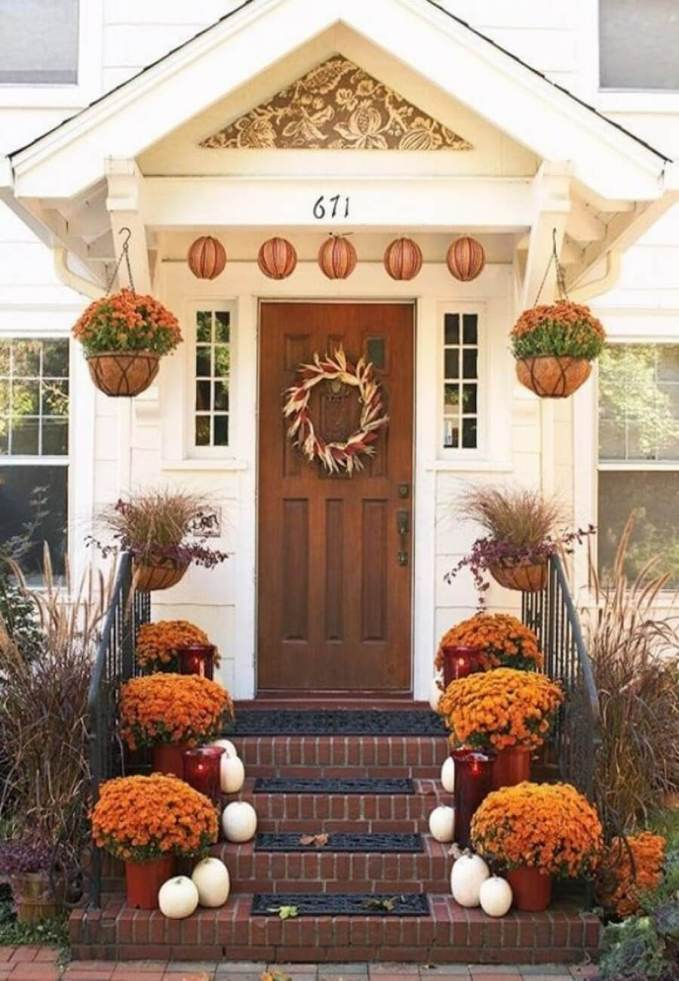 60-Pretty-Autumn-Porch-Décor-Ideas-With-white-wooden-walls-door-window-lamp-hanging-pots-brick-stairs-pumpkin-ornaments