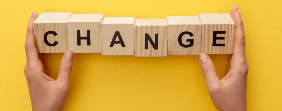 Dos manos colocando unas fichas de scrabble que dicen cambio para ilustrar cómo cambiar a través del coaching