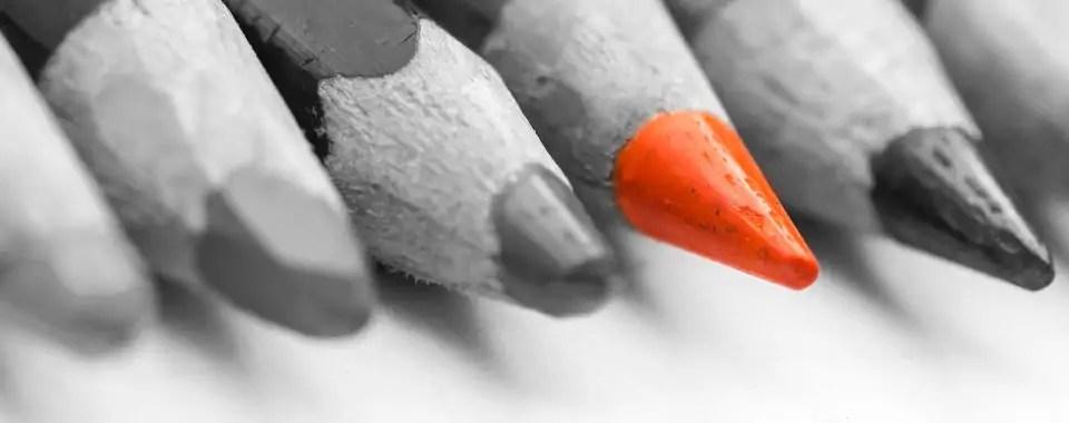 Un lápiz de color naranja resalta sobre un grupo de lápices de color oscuro para simbolizar cómo diferenciarte como coach