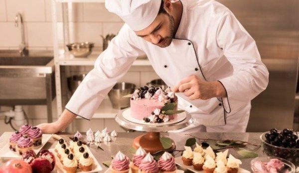 confectioner decorating cake in restaurant kitchen