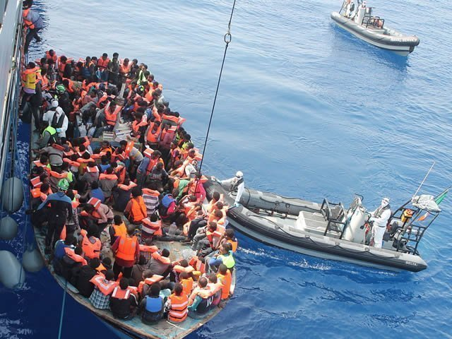 an image of migrants on a boat in the Meditteranean sea