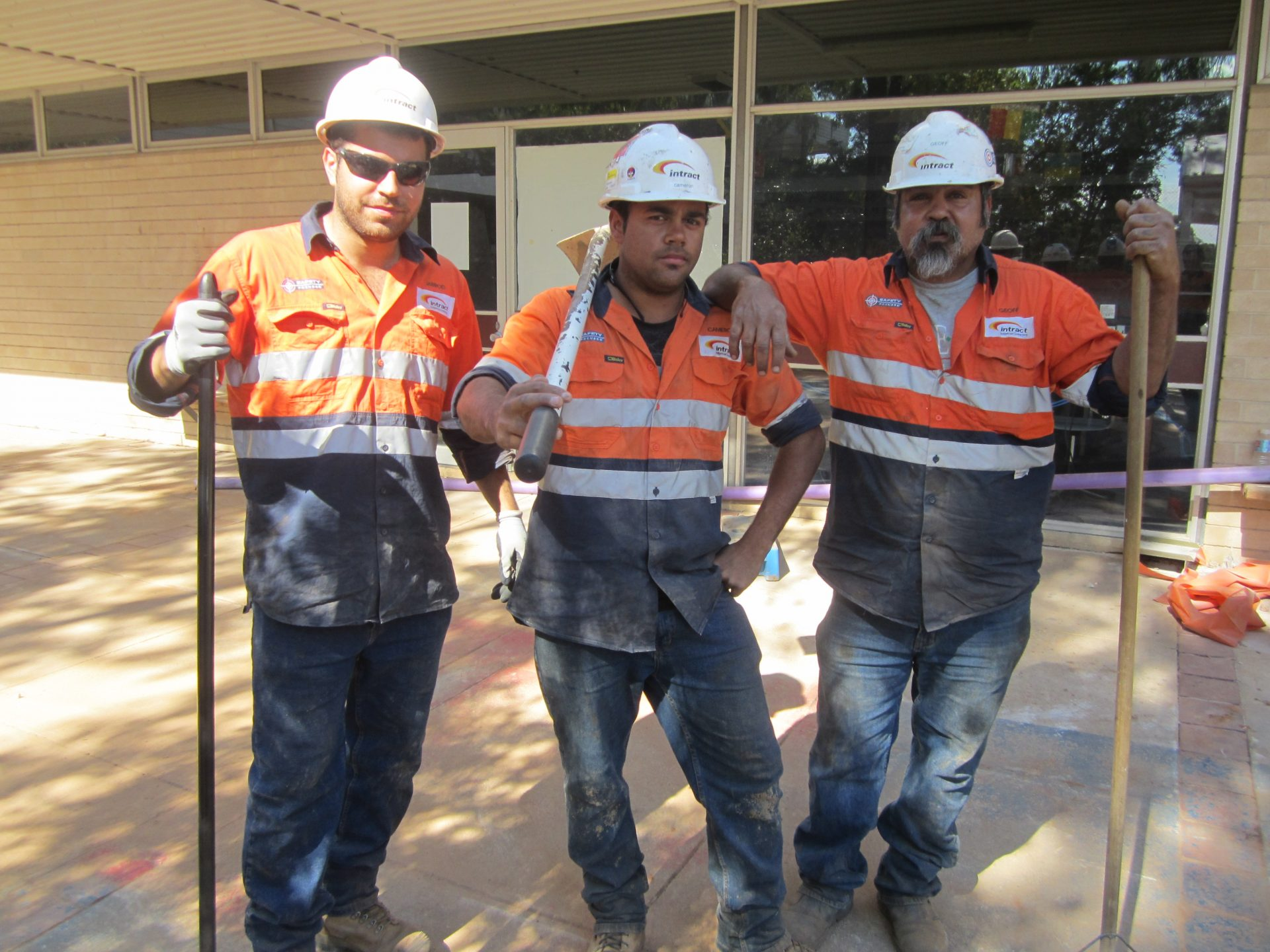 Three Intract contractors standing out the front of building at construction site
