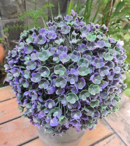 Arbol artificial con base de cemento, color verde con azul. Foto de las hojas.