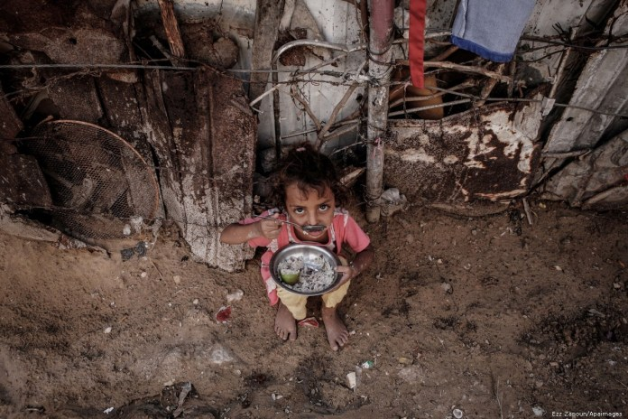 2013 2 2 A Palestinian girl eats outside her familys in a poverty strickenEZZ 00 3
