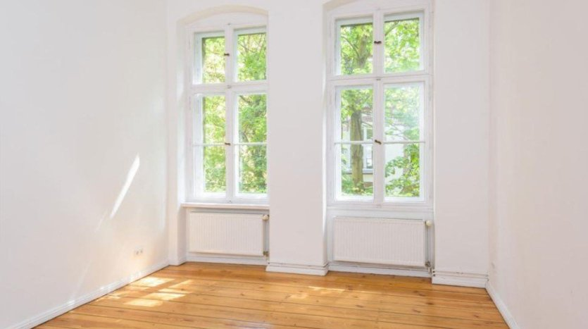 Large room with two big windows, which are oppened on a backyard