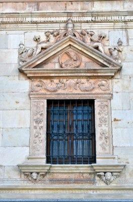 Colegio de San Ildefonso, Alcalá de Henares, ventanas de la planta baja con los padres de la iglesia: San Ambrosio (por Manuel Ramírez Sánchez vía Wikimedia).