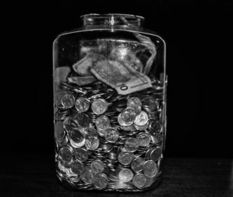 A tip jar full of change - Money Managers