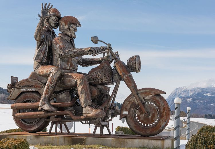 Steel monument of a biking couple on a Harley-Davidson Fat Bob at a roundabout on Rosental Strasse in Faak am See, market town Finkenstein on the Lake Faak, district Villach Land, Carinthia, Austria, EU - Offshore risk