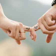 Couple holding hands with tatoos on fingers - retirement