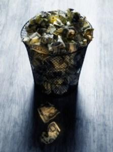 Wastebasket Filled with Crumpled Dollar Bills