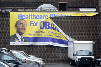 "A ""Healthcare Workers for Obamacare"" sign hangs torn in a parking lot in New York on Oct. 31, 2012.  AP"