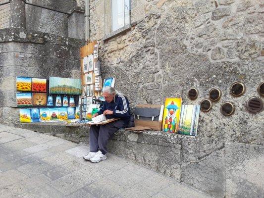 Artista che espone le sue opere nei vicoli di San Marino