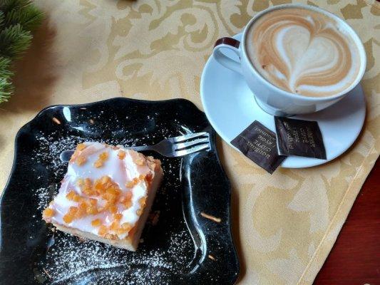 Una fetta di torta e un cappuccino in un caffè di Breslavia