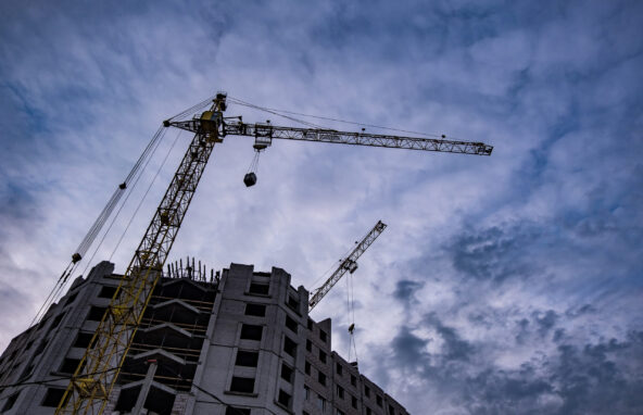 Tower cranes and unfinished multi-storey high buildings under construction site in the evening with dramatic colorful cloud background