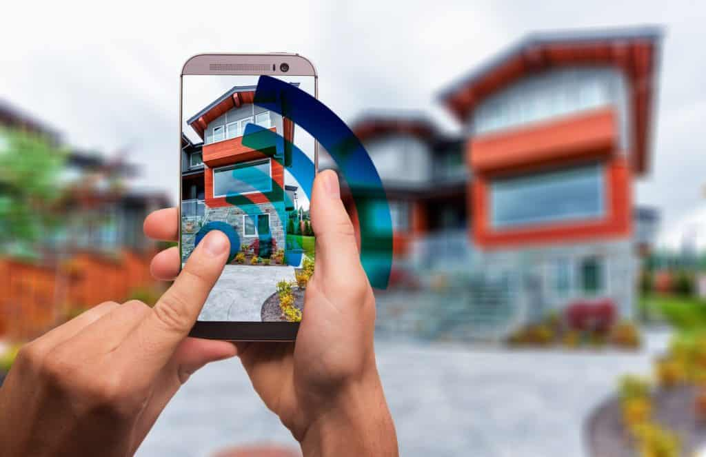 Graphic of two hands utilizing a mobile phone to take a picture of a house.