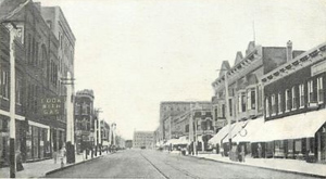 Postcard view of businesses facing E. 4th Street in Waterloo